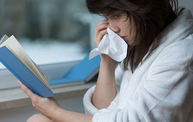 Na imagem vemos uma mulher que está lendo livros que abordam o luto.