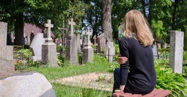 Mulher no cemitério pensando no sepultamento ou cremação